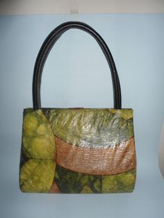 Bolsa de caixa tetra pak e filtro de café tingido. Impermeabilizada interna e externamente. Fechamento com fecho magnético. Alça em couro.
