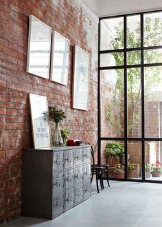 J'aime : le mur en briques, le meuble en métal, la baie vitrée à cadres noirs.