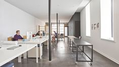 The architecture studio for Collective Office has polished concrete floors, a black feature wall, and white tables.