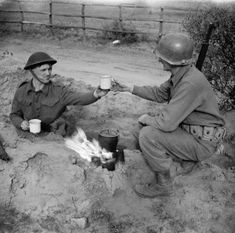 A soldier with the 2/7th Middlesex Regiment shares a cup of tea with an American infantryman in the Anzio bridgehead, 10 February 1944.