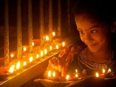 Cute girl lighting diyas.