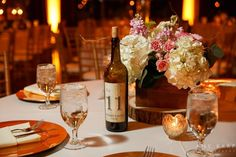 Guest table with wine bottle table number and gold chargers - Photo by Amy Karp Photography