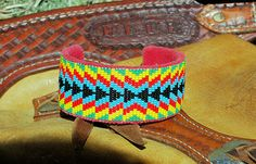 This awesome Bright Colored cuff is large enough for a male wrist or can be fitted smaller for a female's wrist. Great Geometric Design will stand out in a crowd! It is woven on-loom using #11 seed beads in an awesome and colorful geometric native inspired design. It is attached to a