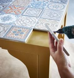 The top of a gold IKEA LACK table is being decorated with decorative tiles.