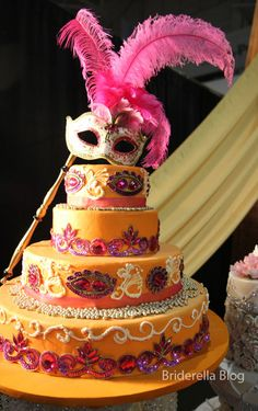 A Masquerade inspired wedding cake in orange, hot pink and purple.