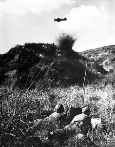 """A marine air-observer team guides a marine Corsair in for a strike on an enemy-held hill. The """"black Corsairs"""" were highly praised by army and marines alike for their precision strikes on targets and their extremely close support of forward units. (U.S. Marine Corps photo.)"""