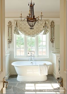 This bathroom is amazing! I love the window treatments, the chandelier and that tub....