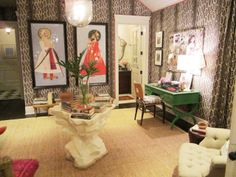 Alternative view of the sitting room in the Windsor house with Peter Dunham's animal print Gattapardo linen fabric on the walls and matching floor length curtains, on the walls are two paintings in black frames, a lacquered green desk, dark wood floor, a rockery inspired center table and a sea grass rug