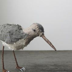 sandpiper feathered from layers of vintage fabrics with a hand carved beak. she's perched on long wrapped wire legs.