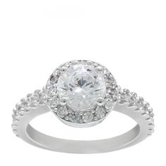 This romantic, yet inexpensive engagement ring from our 10k value line is your dream come true! A 1.24 carat Round Brilliant cut diamond simulant center stone is surrounded by a halo of accents to make it look even grander, while the jewels in the band's shoulders give it an extra elegant touch.   Center Stone: 1.24 carats 1.73 total carats 28 Round Brilliant cut Diamond Simulant accents Shown here in 10k gold. 4.45 grams Looking for a matching band? Contact the Nexus Design Studio to have…