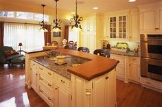Custom birch cabinetry from Plato Woodwork features a painted buttercream finish with a brown glaze