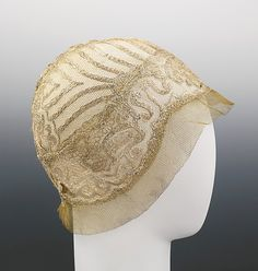 Gold net evening cloche with gold embroidery, by Jeanne Lanvin, French, ca. 1925. This hat features gold embroidery in concentric lines and wave patterns inspired by Chinese Imperial robes of the Qing dynasty. Sheer hats with shimmering decorative elements were favored for evening wear; they drew focus to the face and were a replacement for jewelry at neck and ears.