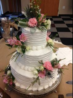 3 tired wedding cake with a simple ridge design decorated with pink alstroemeria, carnations, blue thistle and white spray roses. Cake designed by Flowers by the Bunch