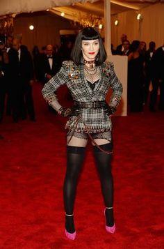 Madonna deixou de lado o longo e preferiu uma fantasia que faz jus ao tema da festa, mas não à elegância do red carpet. O vestido curto e xadrez foi combinado com um scarpin rosa e peruca preta.