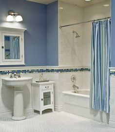 White subway tile + white mosaic floor, and blue mosaic accent. accent runs from chair-rail height all around room. notice the accent tiles have a solid line of blue through the middle.