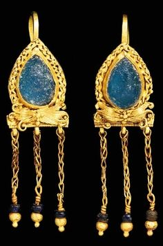 A PAIR OF ROMAN GOLD AND GLASS EARRINGS. Circa 2nd-3rd Century A.D. Each drop-shaped, set with a blue glass and framed by a pair of twisted ribbons punctuated by granules, a bow below of sheet with incised grooves and voluted ends, a cluster of granules in the centre, the lower edge with a beaded wire border from which is suspended three lengths of loop-in-loop chain, each terminating in a glass bead and a large and small hollow sphere, a hooked ear wire in back.