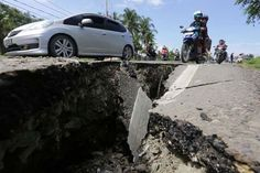 Motorcyclists pass a damaged section of a road following an earthquake in Meuredu Pidie Jaya in the northern province of Aceh Indonesia