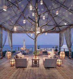 Piccolo terrazzo illuminato  Angolo relax di un terrazzo dalla luce soffusa. Sfere luminose  Come illuminare il terrazzo con le sfere luminose appese. Terrazzo al mare  Idee per illuminare il terrazzo di una casa al mare.