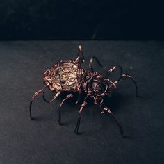 My mechanical spider, an handmade creature. Made with a clock motor, a garnet gemstone and enameled copper wire.