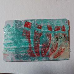 Background gelli print with red flower stamp on top.