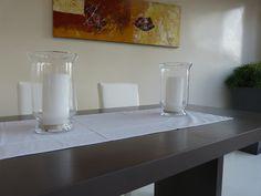 Mesa de microcemento chocolate y pared de microFine blanco perla, acompañada de velas blancas en jarrones itwiz de cristal