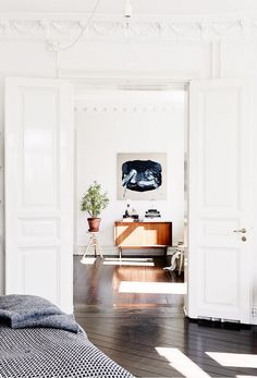 White walls, white doors, blue wall art, wood cabinet, brown planter, and hardwood floors