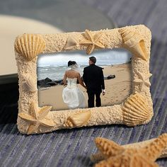 Sand & Shell Photo or Placecard Frame (FashionCraft 6415) | Buy at Wedding Favors Unlimited (http://www.weddingfavorsunlimited.com/sand_shell_photo_or_placecard_frame.html).