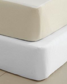 An elegant solution for concealing a box spring, this cover has a skirt of diamond-patterned cotton matelasse and a platform of cotton percale. Elasticized all around, it will fit box springs up to 12 inches. Portugal.