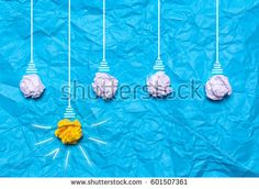 Creative idea of crumpled paper. A burning light bulb on a blue background. Education concept.