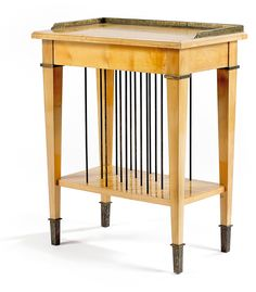 Eugène PRINTZ (1889-1948) & SAINT-GEORGES Petite table d'appoint néo-classique,à structure en merisier,piétement gaine s'élevant de hauts sabots en laiton patiné à l'acide et bordé d'une collerette débordante,chapiteaux à l'identique,elle ouvre par un tiroir en ceinture,la tablette inférieure présente une succession de tiges de laiton,délimitant des casiers verticaux,le plateau,allégé d'une cannelure en bordure,est bordé sur trois côtés d'une galerie de laiton patiné à l'acide.61,2x50x30 cm