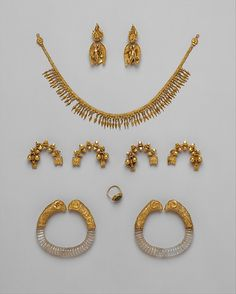 Ganymede jewelry    Period:      Hellenistic  Date:      ca. 330–300 B.C.  Culture:      Greek  Medium:      Gold, rock crystal, emerald  Dimensions:      length of necklace 13 in. (33 cm); H. of earrings 2 3/8 in. (6 cm); width of bracelets 3 1/8 in. (8 cm); width of fibulae 1 15/16 in. (5 cm); H. of ring 13/16 in. (2.1 cm)  Classification:      Gold and Silver