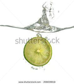 Lime slice splashing water - stock photo