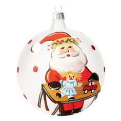 The Old St. Nick Ornament with Worktable and Toys is presented in a clear box for gift giving. The ornament, painted in classic holiday colors of red, green and white, shows Old St. Nick putting together some children's toys.