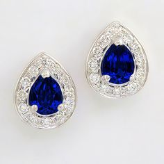 Intense cornflower blue Tanzanite pears set with a classic halo of fine Diamonds. The ultimate pair of Tanzanite and Diamond Studs.