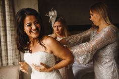 Bride putting on her beautiful strapless wedding dress, helped by her friends and family Pembroke Lodge Wedding Photography Richmond. Image by ARJ Photography