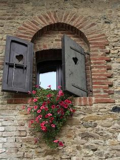 window with petunias, wooden shutters, stone house,  in  Piacenza, Italy. By Di Vinti