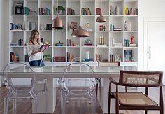 A arquiteta Gabriela Marques desenhou a estante branca, dividida em nichos, para a sala de jantar. A mesa de laca branca tem a mesma cor e é rodeada por dois tipos de cadeira: algumas são de madeira e palhinha e as outras, transparentes, com design de Philippe Starck
