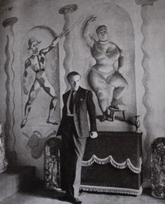 """Cecil Beaton in the Circus Bedroom at Ashcombe.  The """"Fat Lady"""" in the mural behind Beaton was painted by his friend, Rex Whistler."""