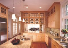 Kitchen with light wood cabinets and brick back splash in Craftsman style home designed by Stuart Cohen & Julie Hacker