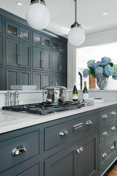 Gray kitchen features white glass globe pendants illuminating gray island topped with white marble countertop and white marble backsplash framing gas cooktop situated in front of floor to ceiling gray cabinets.