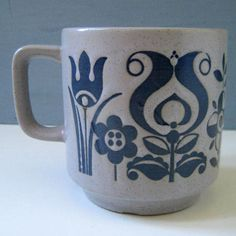Folk art. Vintage stoneware mug. Stylized blue flowers will make your tea feel very retro indeed.