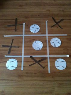 Baseball Tic-Tac-Toe game for Baseball Party.  Use masking tape for grid lines.  X's are bats crossed and of course the O's are baseballs!
