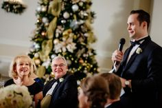 Parents of the groom listen to best man's toast at wedding with gold Christmas decor