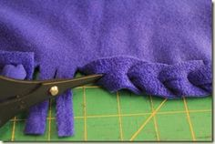 "NO-SEW QUICK AND EASY FLEECE BLANKET EDGING: Cut 1"" slits around the edge of the blanket and a 2"" square out of each corner.   Slip a crochet hook through the slit in one strip then into the slit of the next one in line. Next put the crochet hook through the slit in the next strip and pull it through….keep doing this all around the throw until you only have one strip left. This edging is so quick and easy, and looks like a crocheted or woven edge yet it is much easier to achieve."