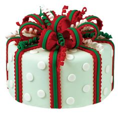 Holiday wrapping starts now! Add a festive touch to this cake with seasonal colors, fun cut outs, cute curlicues, and a magnificent ribbon striped bow. Watch our online video.