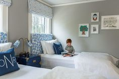 Twin beds placed in front of windows in small bedroom with coordinating fabrics on headboards & shades