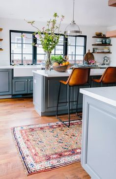 This kitchen is amazing- oozing with texture and personality without being buzy or over done.  Vintage rug, gray cabinets, camel leather stools, and open shelving.