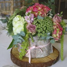 Rustic table centre wrapped in bark. beautiful hydrangeas are teamed with lilac roses, trailing green amaranthus, scented stocks and fresh eucalyptus foliage.
