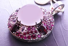 "multicolourgems: "" Like a crystal ball, a large Brazilian star quartz is encircled with an assortment of African rhodolites to create an amazing parade of color. The hinged clasp makes the piece easy to use as a pendant or an enhancer. Looks stunning..."