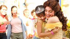 Princess Belle hugs a girl wearing a Disney Princess headband